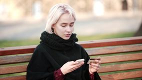 Happy Blonde girl outside Performs transaction this gold payment debit credit card to the smartphone. Blonde woman girl outside. In the hands of a smartphone and stock footage