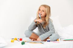 Happy blonde girl with pencil in her mouth sitting in bed, looki. Ng at camera Royalty Free Stock Photos