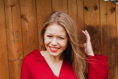 Happy blonde girl with red clothes and lips Royalty Free Stock Images