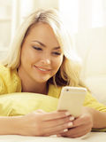 Happy blonde girl with a smartphone at home Stock Photos