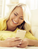 Happy blonde girl with a smartphone at home Royalty Free Stock Photo