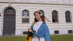 Happy blonde girl smiling is holding in hands a notebook and listening to music with headphones. view against the. Background of the school. Concept of stock video footage