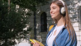 Happy blonde girl smiling is holding in hands a notebook and listening to music with headphones. view against the. Background of the school. Concept of stock video