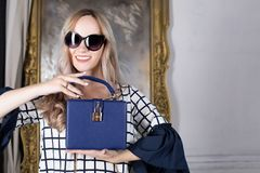 Happy blonde woman in sunglasses holding blue leather purse. Spa royalty free stock images