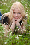 Happy blonde girl surrounded by flowers. Happy blonde girl in the field surrounded by flowers Royalty Free Stock Photos