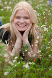 Happy blonde girl surrounded by flowers. Happy blonde girl in the field surrounded by flowers Stock Image