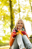 Happy blonde girl teen sitting forest fall. Autumn Stock Images