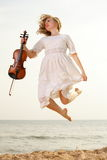 Happy blonde girl with a violin outdoor Royalty Free Stock Photography