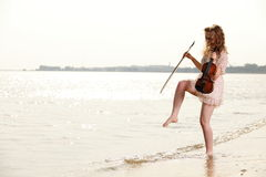 Happy blonde girl with a violin outdoor Royalty Free Stock Image