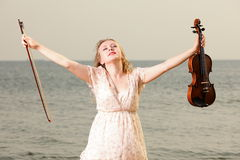 Happy blonde girl with a violin outdoor Stock Images