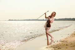 Happy blonde girl with a violin outdoor Stock Photo
