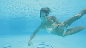 Happy blonde girl in white bikini swims breaststroke and shows a thumb up gesture stock video