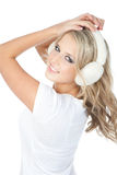 Happy blonde girl in winter headphones over white Stock Images