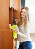 Happy blonde girl wiping the dust Stock Images
