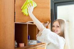 Happy blonde girl wiping the dust Royalty Free Stock Image