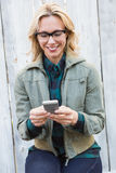 Happy blonde in glasses text messaging Stock Images