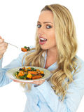 Happy Blonde Haired Cute Young Woman Eating a Roast Vegetable Salad Royalty Free Stock Image