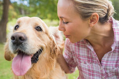 Happy blonde with her dog in the park Royalty Free Stock Image