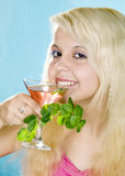 Happy blonde holds in hand aglass and  mint Royalty Free Stock Photos