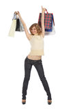 Happy blonde holds paper bags in rised hands royalty free stock image