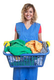 Happy blonde housewife with dirty clothes. On an isolated white background for cut out stock image