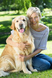 Happy blonde hugging her dog in the park Royalty Free Stock Photography