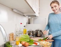 Blonde learning new recipe of vegetables. Happy blonde learning new recipe of vegetables at home Stock Images
