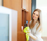 Happy blonde long-haired girl wiping the dust Royalty Free Stock Images