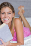 Happy blonde lying on her bed reading a book smiling at camera Stock Photo