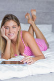 Happy blonde lying on her bed using tablet pc smiling at camera Stock Image