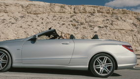 Happy blonde with man driving in the cabriolet. Beautiful blonde with boyfriend driving in the cabriolet. Handsome man sits on the driver`s seat. The car slowly stock video footage