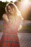 Happy blonde model in fashionable checkered dress posing at the royalty free stock photos