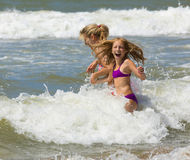Happy blonde mother and daughter play among waves of sea Stock Image