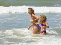 Happy blonde mother and daughter play among waves of sea Royalty Free Stock Photos