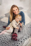 Happy blonde mother embrace her little baby daughter. Cozy home. Royalty Free Stock Image