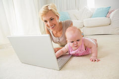 Happy blonde mother with her baby girl using laptop Royalty Free Stock Image