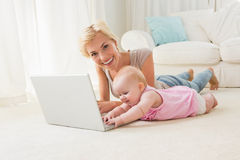 Happy blonde mother with her baby girl using laptop Royalty Free Stock Images