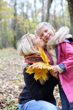 Happy blonde mother kisses her daughter with maple leaflets. Happy blonde mother kisses her daughter with yellow maple leaflets in autumn forest. Shallow depth royalty free stock photo