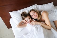 Happy blonde mother lying in bed with little jocund daughter. royalty free stock photography
