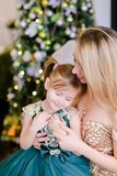 Happy blonde mother sitting with little daughter wearing dress near Christmas tree. stock photos
