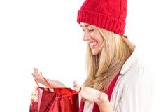Happy blonde opening gift bag Royalty Free Stock Image