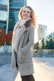 Happy blonde in overcoat standing outside building among autumn. Happy blonde in long overcoat standing outside building among autumn Royalty Free Stock Photography