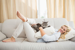 Happy blonde with pet cat on sofa Stock Images