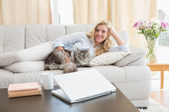 Happy blonde with pet cat on sofa. At home in the living room Stock Image
