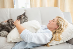 Happy blonde with pet cat on sofa Stock Image