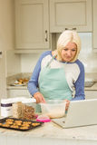 Happy blonde preparing dough following online recipe Royalty Free Stock Photos