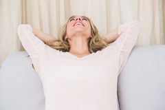 Happy blonde relaxing with hands behind head on couch Stock Photography