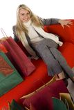 Happy blonde sitting on couch Stock Photography