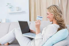 Happy blonde sitting on couch shopping online Royalty Free Stock Photography
