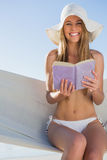 Happy blonde sitting on hammock holding book Royalty Free Stock Photo
